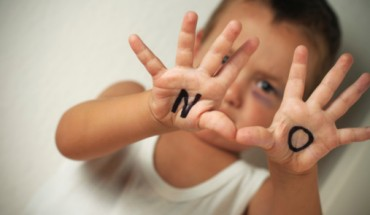 Child victim holding up her hands to say no.
