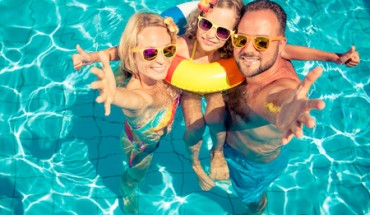 78593390 - happy family having fun on summer vacation. father, mother and child playing in swimming pool. active healthy lifestyle concept